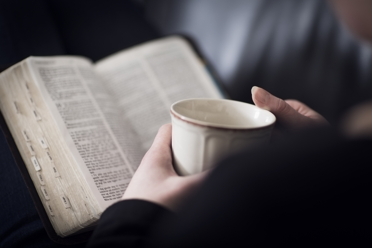 woman reading Bible with cup of tea